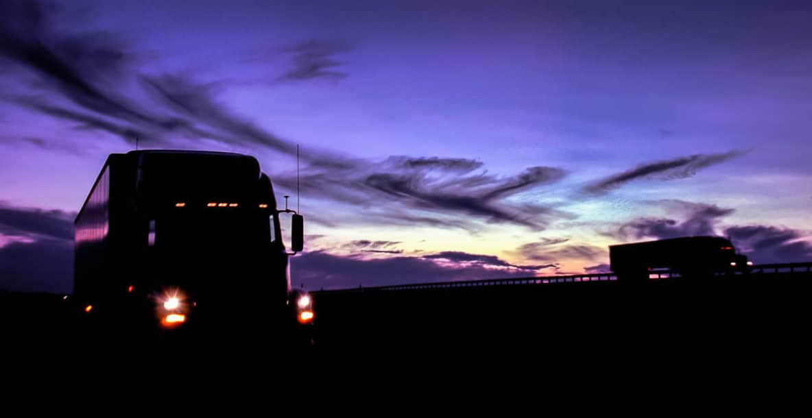 Trucks on road at sunset